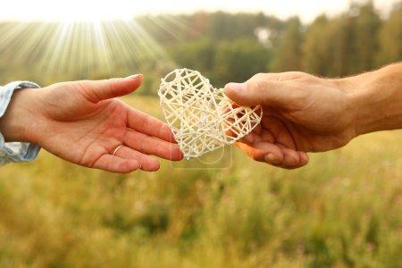 Photo pour Deux mains de couple avec cœur sur la nature - image libre de droit