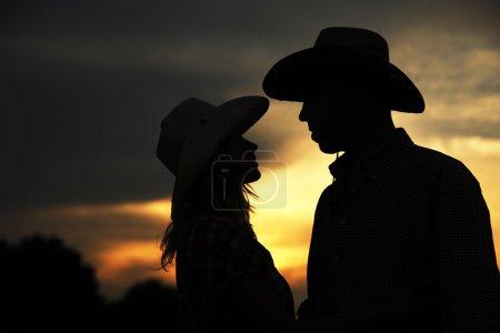 Photo pour Silhouette de jeune couple en chapeaux de cowboy sur coucher de soleil - image libre de droit