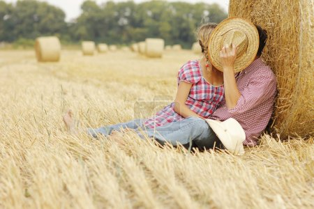 Couple embracing near haystacks
