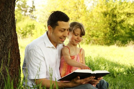 father with daughter reading book
