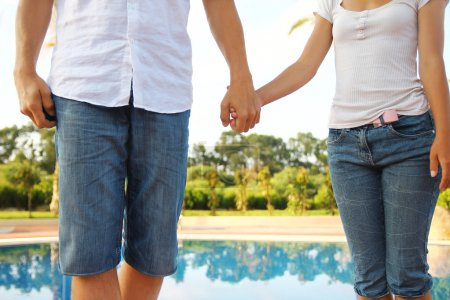 Hands in love couple at pool