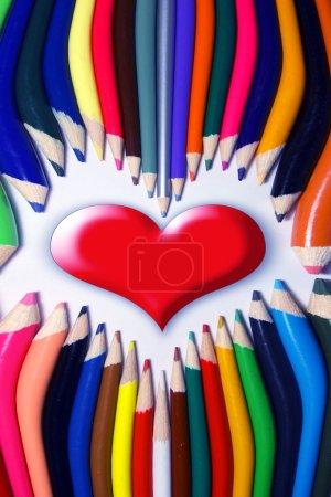 Photo pour Coeur rouge sur fond blanc avec crayons - image libre de droit