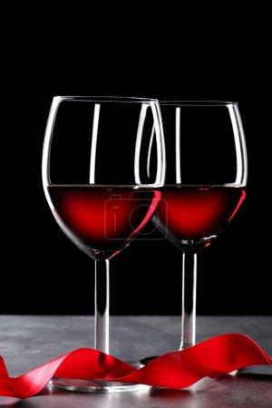 Photo pour Deux verres à vin rouges et un ruban rouge sur table en ardoise et fond noir avec espace de copie pour votre texte - image libre de droit