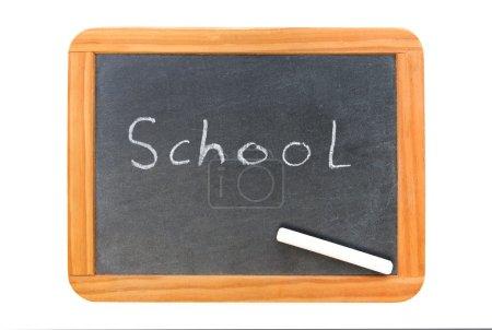 Photo pour École écrite sur un tableau vintage et une craie sur le tableau, isolée sur du blanc - image libre de droit