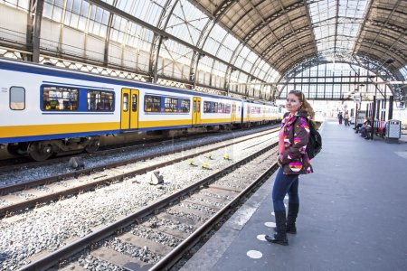 Young woman waiting for the train at central stati...