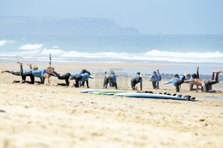 Surfers doing excersises on beach