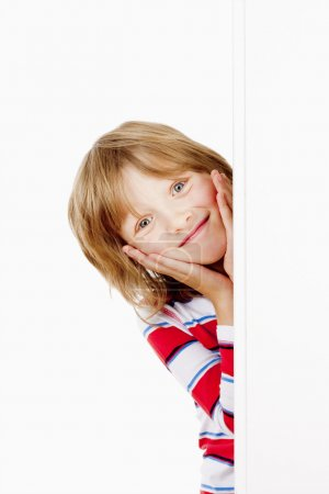 Boy Peeking Out From Behind A White Board Smiling