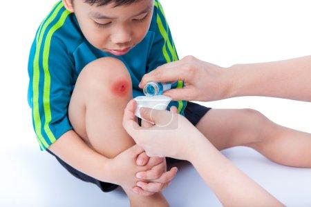 Little asian boy looking wound his leg