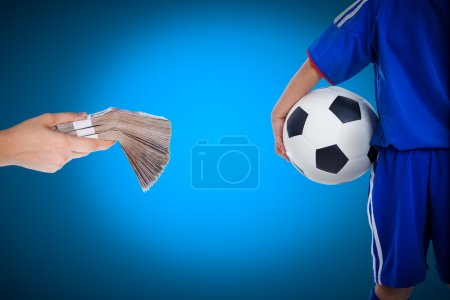 Back view of youth soccer player and hand holding stacks of bank