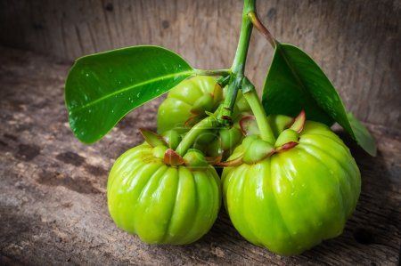 Still life with fresh garcinia cambogia on wooden background