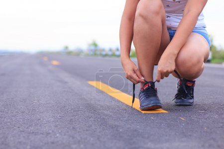 Stock Photo - Close up of girl tying her running shoe laces at s