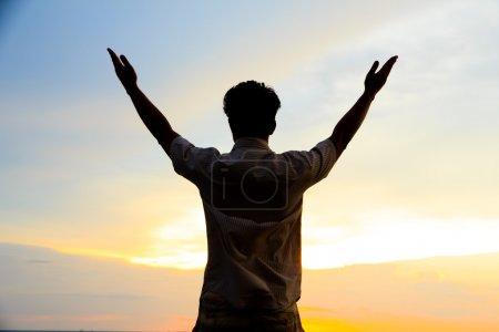 Photo pour La silhouette de l'homme seul au coucher du soleil dans le désert avec les bras tendus - image libre de droit