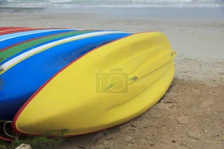 Stock Photo - Row of Kayaks beside the sea