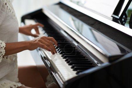 hands fingering piano keys