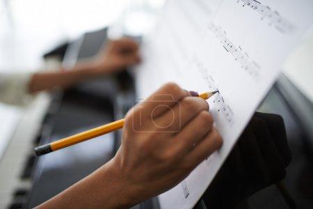 Photo pour Gros plan des mains féminines corrigeant la musique du film. Compositrice - image libre de droit