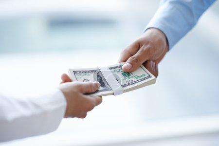 Hands of businessman giving money