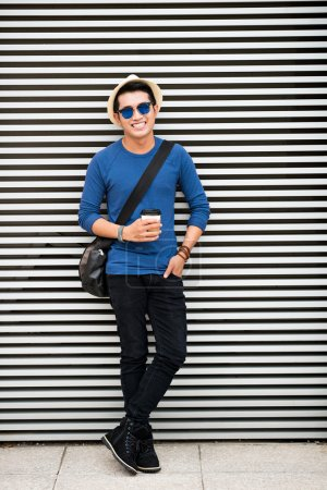 Photo for Cheerful stylish asian guy with coffee leaning on the wall outdoors - Royalty Free Image
