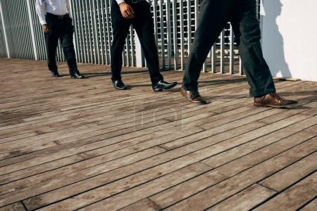 Legs of businessmen walking