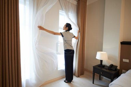 Hotel manager adjusting curtains in the room in ho...