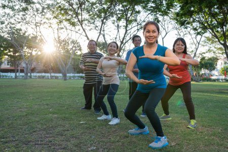 Photo for Vietnamese men and women practicing martial art outdoors. Tai Chi beginners - Royalty Free Image