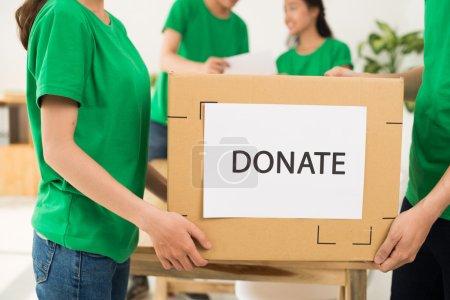 Volunteers carrying donate box