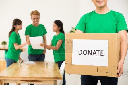 Photo pour Bénévoles d'emballage des boîtes de dons dans le bureau. Notion d'organisme de bienfaisance et dons - image libre de droit
