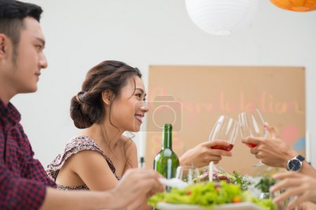 woman clinking glasses with friend