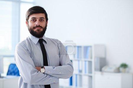 Foto de Seguros barba hombre de negocios de pie con los brazos cruzados - Imagen libre de derechos