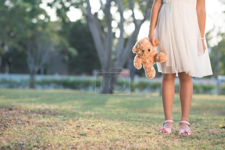 girl carrying toy bear