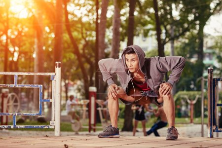 young man doing deep squats