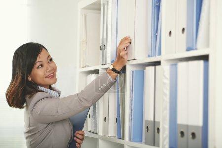 Smiling business woman taking binders