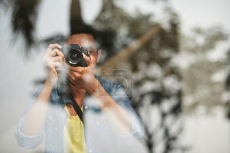 Photographer taking photo through glass