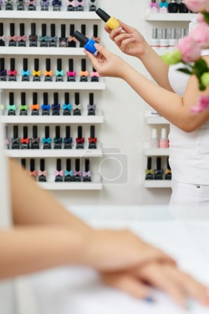 Manicurist choosing nail polish