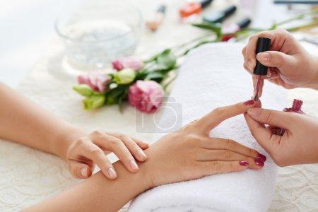 Manicurist polishing fingernails