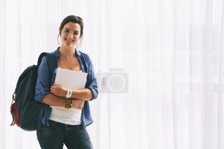Female student with backpack and textbooks