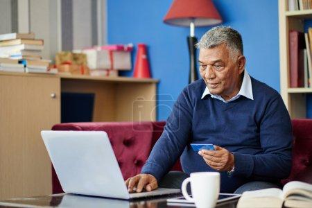 Aged Indian man pying bills