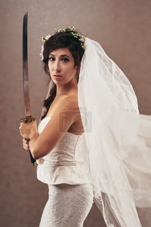 Portrait of determined young bride with katana swo...