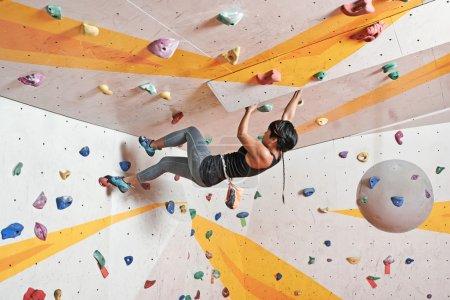 Photo pour Jolie jeune athlète féminine escalade dans la salle de gym - image libre de droit