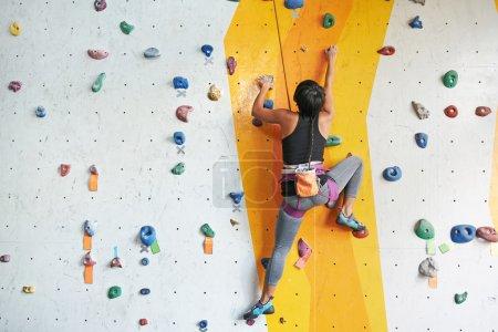 Photo pour Vue arrière de l'escalade sportive dans la salle de gym - image libre de droit