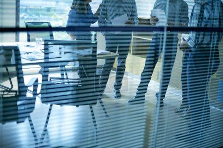 Photo pour Image recadrée de collègues parlant dans la salle de bureau - image libre de droit