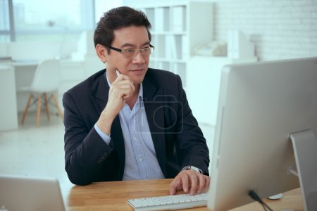 Photo for Mature Asian businessman working on computer in office - Royalty Free Image