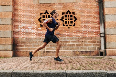 Photo for Side view of running sportsman: healthy lifestyle - Royalty Free Image