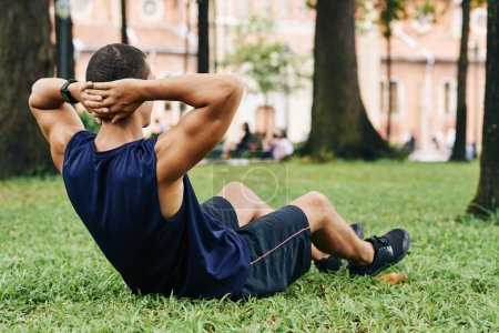 Sportsman doing crunches in park