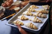 Nő üzembe az tálca croissant sütőben