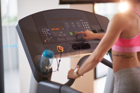woman pushing button on treadmill