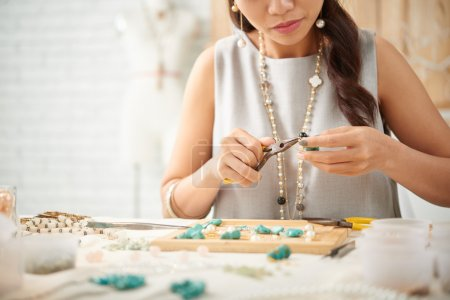 woman concentrated on creation of jewelry piece