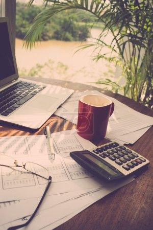 Photo pour Tableau du gestionnaire financier : ordinateur portable, documents, calculatrice, tasse à café et verres - image libre de droit