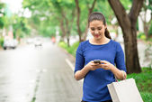 Woman with paper bags texting