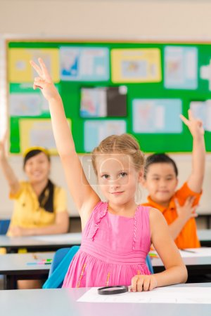 Schoolgirl raising hand at a lesson