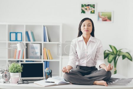 Photo for Female office worker meditating on her work place - Royalty Free Image